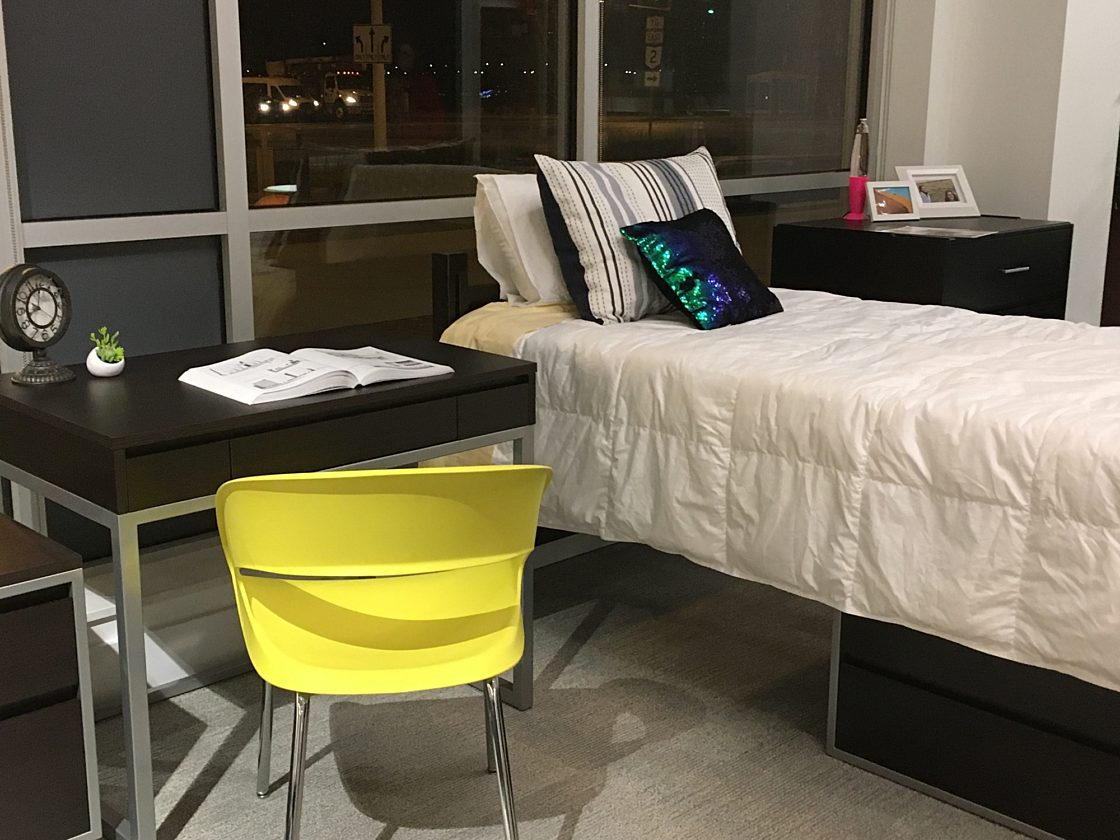 A mock-up of a college dorm bed with a bedside cabinet and a small desk. The space is decorated with colorful pillows and knickknacks.