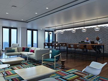 Collaborative gathering space with comtemporary lounge seating, plush rug, bar-height meeting table and richly textured wall.