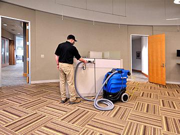 A uniformed worker stands next to a fabric-covered workstation wall. Using a rolling machine, they spply disinfectant to the furniture.